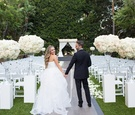 groom in lanvin, bride in reem acra hold hands outside classic outdoor ceremony