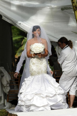 Bride in a strapless form-fitting gown with Swarovski crystals and pearls, veil, and white bouquet