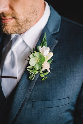 Navy blue groom suit with green and white boutonniere