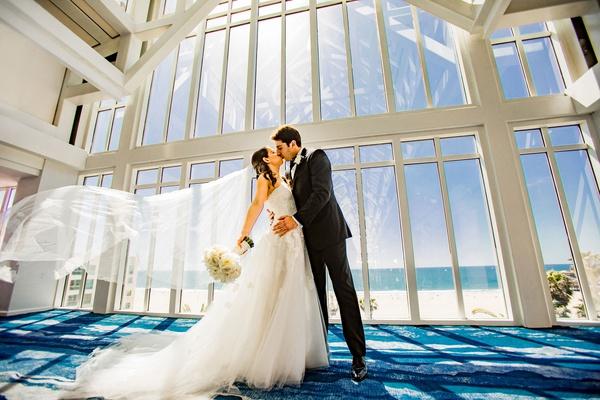 wedding photo bride in white strapless dress kissing groom veil blowing in wind ocean view window