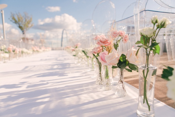 white aisle runner lined with crystal vases filled with pink and white roses outdoor wedding