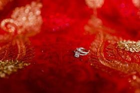 radiant-cut diamond ring with pavé ring on red sari fabric