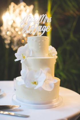 Fresh orchid flowers and laser cut calligraphy cake topper on small white cake with pearl decoration