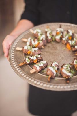 za'atar spiced lamb sirloin, red onion, bell pepper skewer, lemon tahini sauce on wood tray wedding