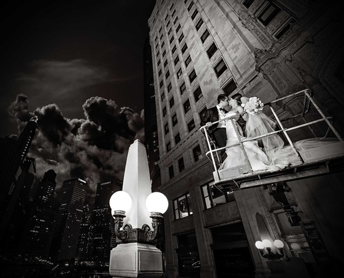 black and white photo of couple on cherry picker in city of chicago in an embrace