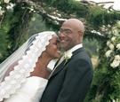 Bride smiles towards groom in front of chuppah