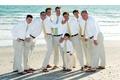 Groom and groomsmen in flip flops on beach