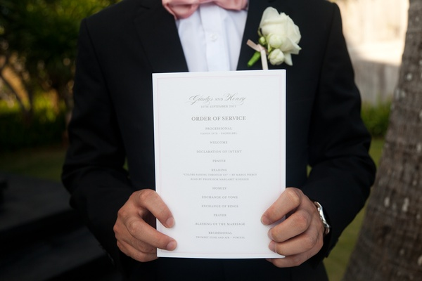 Groom holding one sheet wedding program
