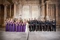 Bridesmaids in purple dresses and groomsmen in tuxes