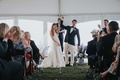 bride and groom clasp hands and raise during tented wedding ceremony blue white vase guests clapping
