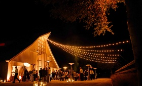 Outdoor cocktail hour with string lights in front of barn