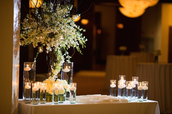 Wedding reception with place card table decorated with white orchids and roses, and floating candles