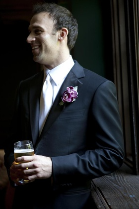 Groom in black suit and white tie with beer