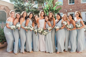 bride in j. mendel wedding dress, bridesmaids in misty blue dessy and adrianna papell dresses