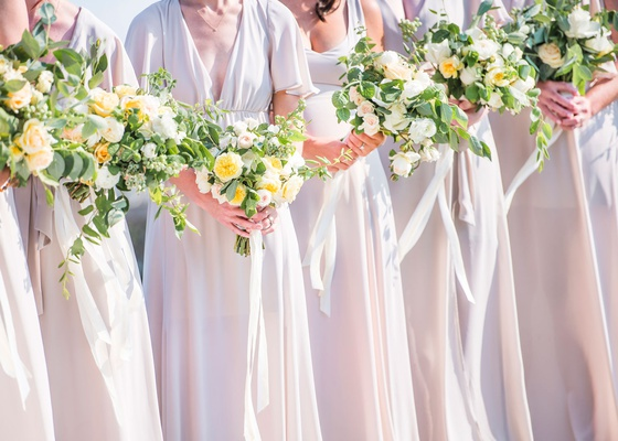 wedding details yellow and light pink flower bouquets with ribbons for bridesmaids neutral gowns