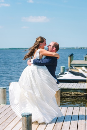 bride in striped hayley paige wedding dress with groom in navy suit on private dock