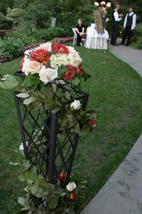 Garland wrapped riser with red and white flowers