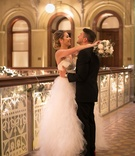Bride in strapless wedding dress tulle layer skirt hugging groom bouquet winter low bun