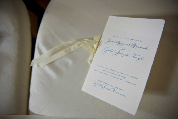 Wedding ceremony program with blue type, off-white ribbon