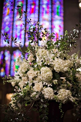 White rose and hydrangea arrangement in front of stained glass window