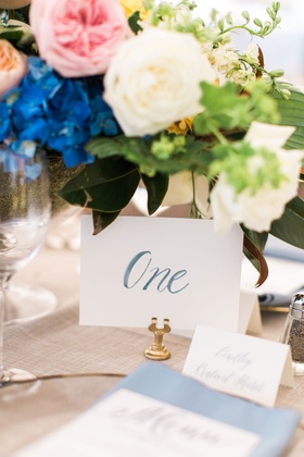 wedding reception gold stand card holder table number with blue calligraphy under low centerpiece