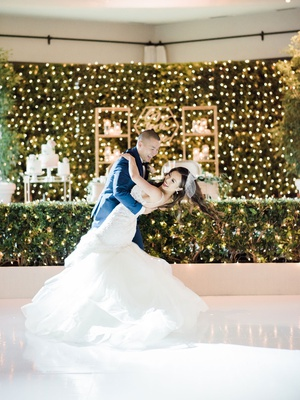 groom in navy blue tuxedo suit dipping bride during first dance vintage birdcage veil
