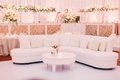 Wedding reception lounge furniture white tufted sofa with light pink and tan pillows pink roses