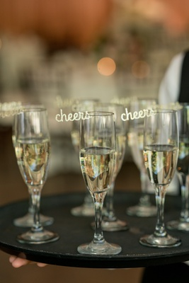 laser cut gold cheers embellishment attached to champagne glasses