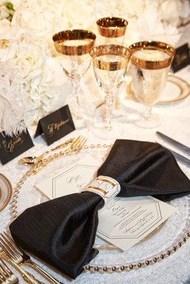 Place setting with white table cloth, black napkin, gold flatware charger plate glassware bow detail