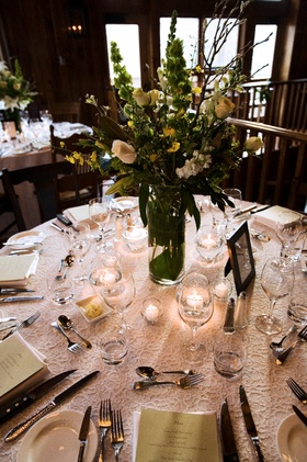 white table with green and yellow centerpieces and green menus