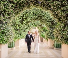 las vegas wedding at the bellagio, bride and groom portrait under arches of greenery & white blooms