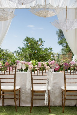 lace fabric on brides chair with light pink roses and lace parasols hanging overhead