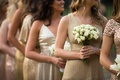 bridesmaids in mismatched gold dresses, bridesmaid carrying nosegay of white roses