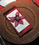 Brown rattan charger with red napkin and orchid