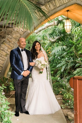 Bride in mermaid Monique Lhuillier wedding dress and lace trim veil with Celio in blue suit jacket