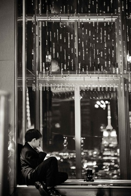 Black and white photo of young boy looking out window to views of New York City wedding reception
