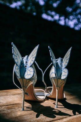 a brides light blue high heels that feature butterfly wings with patterns off of the back