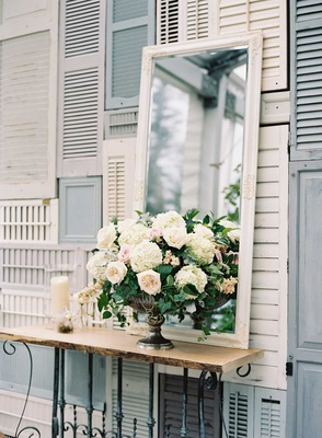 Shabby chic wedding outdoor with wall of white and blue shutters flower arrangement mirror candles