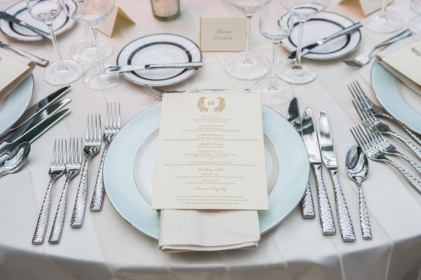 Wedding reception menu with crested monogram on cream napkin and Monique Lhuillier charger