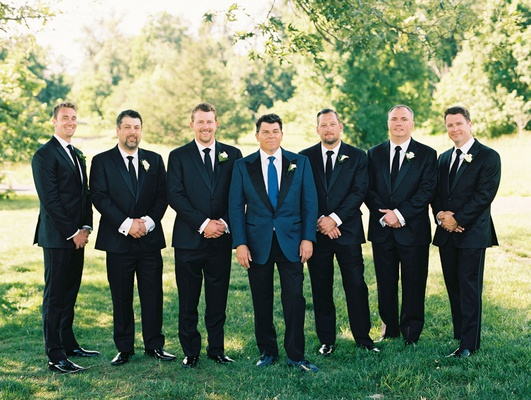 groom in navy tuxedo jacket with black lapels and blue tie with groomsmen in dark suits