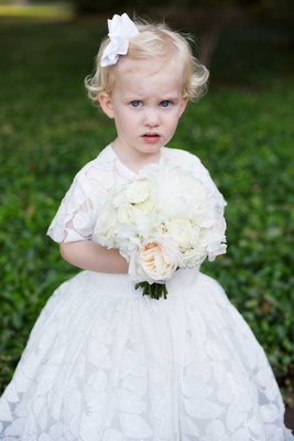 flower girl with blonde hair with white bow white bouquet and white short sleeve ball gown with leaf
