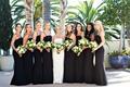 bride in strapless wedding dress bridesmaids in black bridesmaid dresses spaghetti straps greenery