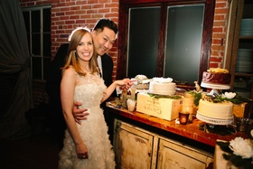 Bride and groom cut into one layer cake at dessert display