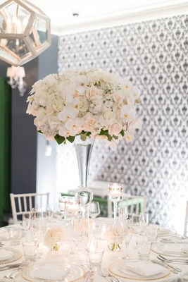 tall glass stand with white orchids and ivory roses, grey patterned wall, geometric chandelier