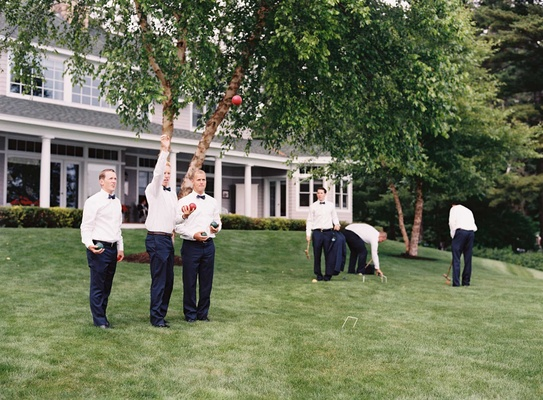 Groomsmen in tuxedos playing croquet and lawn games at family lake house in New Hampshire