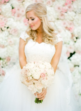 Bride in a Monique Lhuillier gown with lace bodice and tulle skirt with pink and white bouquet