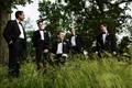 Groom and groomsmen in black tuxedos on the grounds of Sleepy Hollow Country Club
