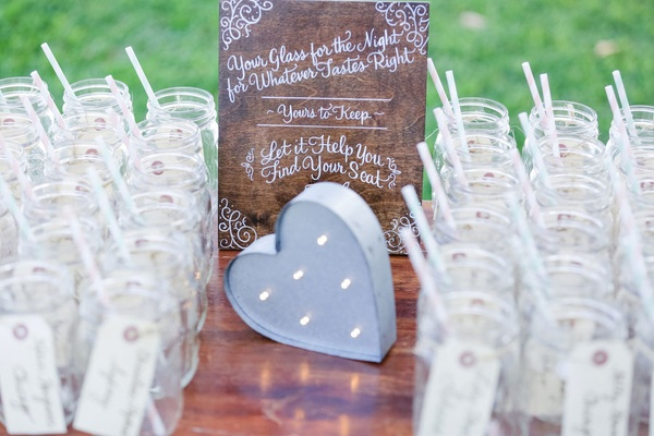 Wedding table numbers on mason jars for drinking at wedding reception with calligraphy wood sign