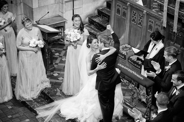 black and white photo of a couple embracing at the i dos ceremony groom raising fist to celebrate
