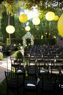 Modern wedding ceremony in garden with yellow lanterns